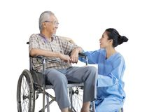 Old man sits on wheelchair and talk with nurse. Asian old men sitting on wheelchair while talking and smiling with his nurse in the studio, isolated on white stock photos