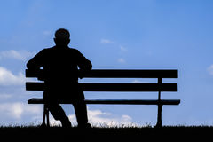 Old man sitting alone on park bench under tree Royalty Free Stock Photography