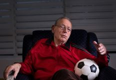 Old man with soccer ball watching tv. Old man sitting in armchair at home, holding soccer ball and watching football match on tv. Feeling disappointed Royalty Free Stock Images