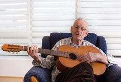 Old man playing guitar at home Stock Image