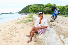 Old man sitting on beach. Old Indonesian man sitting on beach by sea with blue motorbike behind, Labuan Bajo, Flores, Indonesia Stock Images