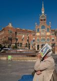 Old man sitting on bench near the beautiful building of Sant Pau Hospital in Barcelona, Catalonia, Spain stock images