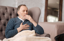 Old man sitting on couch and coughing. Terrible bronchitis. Senior handsome man is coughing really strongly while sitting on couch at home and stock images