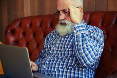 Old man sitting on couch and working with laptop Royalty Free Stock Images