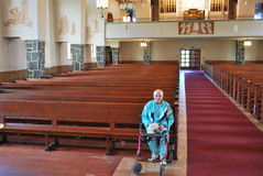 Elderly man sitting in an empty church. Elderly man sitting in a first pew inside  of large empty church Stock Image