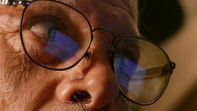 Old man reading the computer screen. Old man sitting in front of the computer with reflection of the computer screen in his reading glasses stock footage
