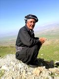 An old man. Sitting on a hill wearing a traditional kurdish cap stock photography