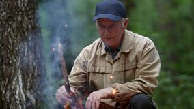 old man is sitting near campfire in forest, resting in camp during trekking, portrait