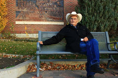 Old Man Sitting on a Park Bench. Old man wearing a cowboy hat sitting on a park bench Royalty Free Stock Photos