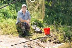 Old man sitting on riverbank fishing Royalty Free Stock Image