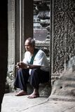 Old man sitting in a stone temple royalty free stock images