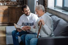 Old man sitting with a volunteer and looking at his favorite book. Wonderful book. Cheerful senior men looking glad while sitting on a sofa with a kind attentive Royalty Free Stock Photo