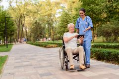 An old man sitting in a wheelchair shows the nurse something on his tablet. The older generation and new technologies. An old men in a wheelchair shows the nurse Royalty Free Stock Images