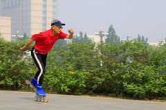Old man skating fitness in a park, china Stock Photo