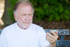 Old man skeptical of text message Royalty Free Stock Photo