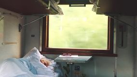 Old man is sleeping in the train. Concept travel train wagon journey interior. Economy wagon railway view from inside. Indoors. Railway interior passenger stock video footage