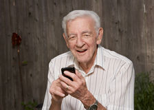Old man with smart phone. Smiling 90 year old senior old man on mobile smart phone royalty free stock photos
