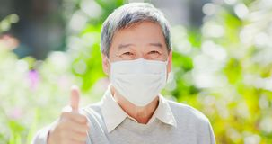 Old man thumbup with mask. Old man smile show thumb up and wear mask with nature green background royalty free stock photos