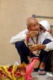 An old man smoking along the street in Hong Kong Stock Photos