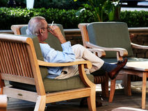 Old man smoking in a chair Royalty Free Stock Photography