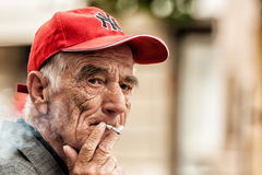 Old man smoking a cigarette on the bench in Zagreb center square Stock Photos