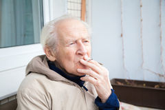 Old man smoking a cigarette Stock Photos