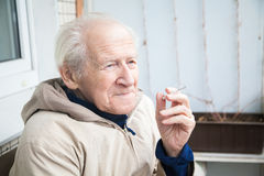 Old man smoking a cigarette Royalty Free Stock Image