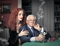 Old man smoking while playing poker Stock Images