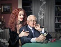 Old man smoking while playing poker Stock Images