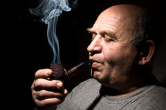 The old man smoking tobacco pipe Stock Photo
