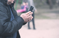 Old man smoking and use his phone. In the park Royalty Free Stock Images