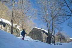 Old man snowshoeing in Alpine trail. Piedicavallo, Piedmont, Italy - February 26, 2015: Old man snowshoeing over snowy Alpine trail stock photos