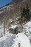Old man snowshoeing in Alpine trail. Piedicavallo, Piedmont, Italy - February 26, 2015: Old man snowshoeing over snowy Alpine trail stock photography