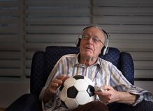 Old man with soccer ball watching tv. Happy old man with remote control and soccer ball sitting in armchair at home and watching football match Stock Photography