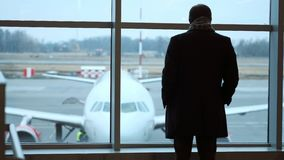 Old man stand at full height, gaze out airport terminal window, silhouette view. Looks at the plane at the airport. Old man stand at full height, gaze out stock footage