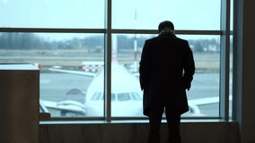Old Man stand at full height, gaze out airport terminal window, silhouette view. Looks at the plane at the airport. Old Man stand at full height, gaze out stock video footage