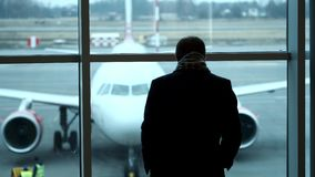 Old Man stand at full height, gaze out airport terminal window, silhouette view. Looks at the plane at the airport. Old Man stand at full height, gaze out stock video