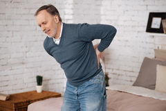 Old man standing with backache. Very sudden. Senior man feeling discomfort while standing because of pain in back Royalty Free Stock Photo