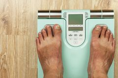 The old man is standing on a modern scale. Measuring the fat content of the body. Intelligent medical weight. The concept of obesi Royalty Free Stock Images