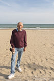Old man standing on sandy beach Stock Photo