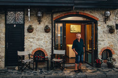 Old man stands near the hotel in the old town of Nessebar and look at passers-by. Stock Photography