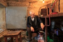 The old man stands in the old wine cellar and boasts wine in bot. Tles stock images