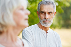 Old man staring pensive at a woman Stock Images