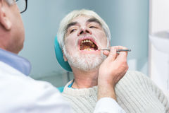 Old man at the stomatologist. Stock Photos