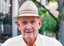 Old Man in Straw Hat. Close-up portrait of senior male wearing a straw hat.  City building and tree in urban park blurred in background. Copy space Royalty Free Stock Images