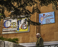 Old man on the street. El Escorial, November 2012. City scene: a man walks on the street near a famous cafe advertising on a facade Royalty Free Stock Photo