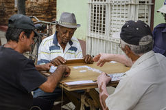 Old man on the street of Trinidad playing domino. Which is typical game for Cubans who often gather to play it outdoor what attracts many tourists Royalty Free Stock Photo