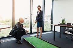 A woman in a black business suit plays golf in the office. An old man in a business suit helps her. The old man, in a strict business suit, teaches his secretary Royalty Free Stock Images