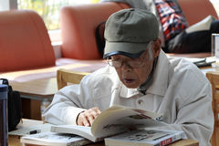 Old man studying in library Stock Photo