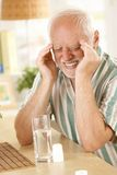 Old man suffering from headache. Eyes closed, grimacing from pain, taking painkiller sitting at table at home Royalty Free Stock Photo